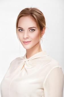 Портрет красивой молодой чувственной блондинки в белой рубашке, улыбающейся и смотрящей в камеру