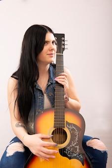 흰색 배경에 어쿠스틱 기타와 함께 아름 다운 젊은 섹시 한 여자의 초상화
