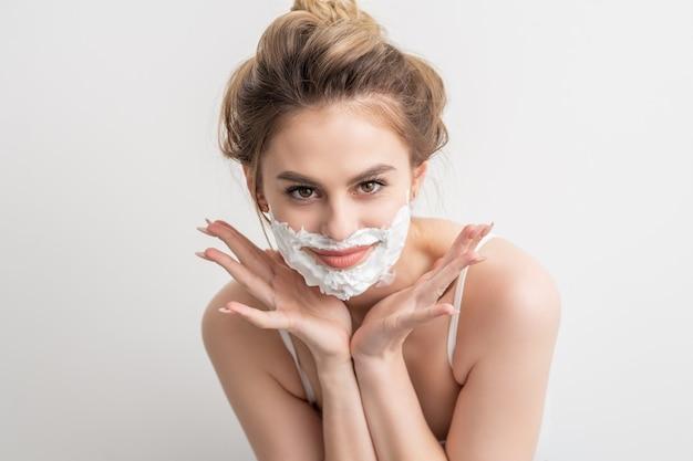 白い背景の上のポーズの顔に泡を剃っている美しい若い笑顔の白人女性の肖像画。
