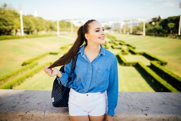 Портрет красивой молодой улыбающейся женщины в зеленом летнем городском парке