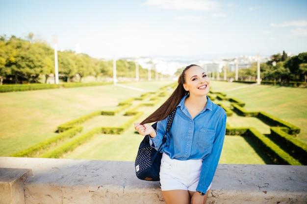 緑の夏の都市公園で美しい若い笑顔の女性の肖像画