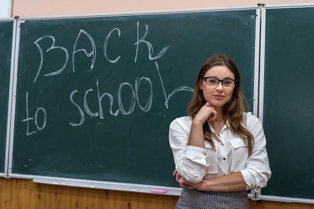 黒板の背景に美しい若い先生の肖像画。学校に戻る。オフライン教育