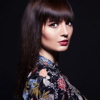 暗い背景の美しい、若い女性の肖像画。
