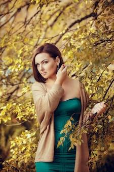 Портрет красивой молодой женщины в осенний парк. картины в теплых тонах
