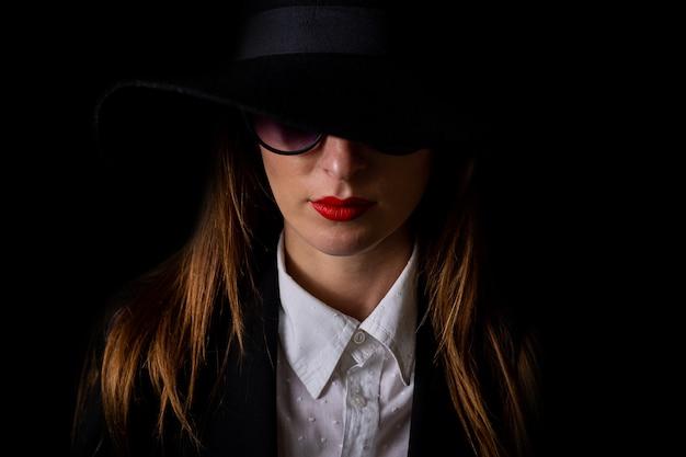 黒の帽子と黒の眼鏡の美しい若い女性の肖像画。