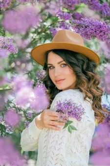 Портрет красивой молодой женщины в цветущем сиреневом парке.
