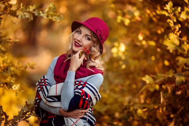 Портрет красивой молодой женщины в бордовой шляпе осенью на прогулке в парке