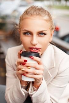 야외 카페에서 커피와 함께 트렌디 한 코트에서 아름 다운 젊은 여자의 초상화