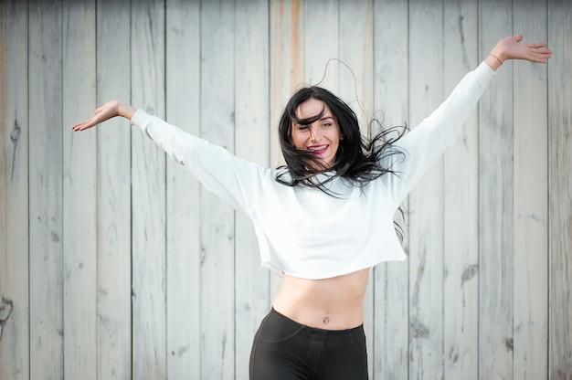黒い髪と白いtシャツを着た美しい若い女性の肖像画。喜びと笑いは退化します。前向きな感情。ライフスタイル。美しさと若さ。白い壁にポジティブで楽しい感情