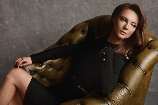 빈티지 가죽 안락의 자에 앉아 유행 검은 옷에 아름 다운 젊은 여자의 초상화