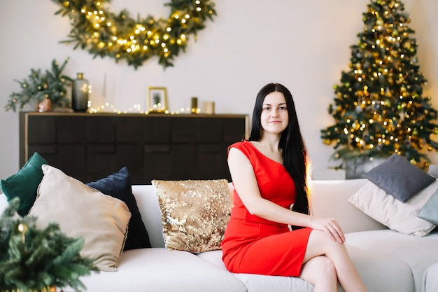 お祝いのクリスマスと新年のインテリアで美しい若い女性の肖像画 Premium写真