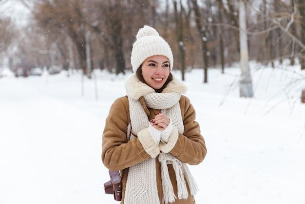 Портрет красивой молодой женщины в шляпе и шарфе, прогулки на свежем воздухе в зимний снег.