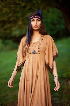 伝統的なドレス、孤立した緑の背景の美しい若い女性の肖像画