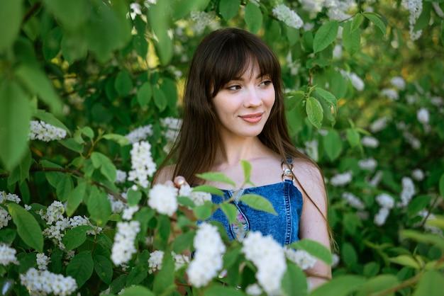 開花鳥桜の茂みを背景に美しい若い女性の肖像画
