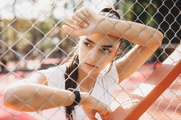 スポーツパークで有酸素運動をした後に休んでいる美しい若い女性の肖像画。