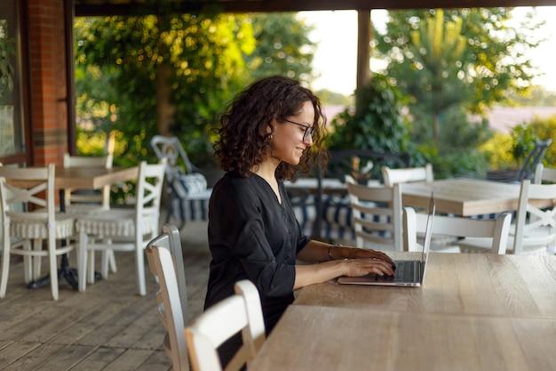 ノートパソコンで入力してテーブルに座っている美しい若い女性の肖像画