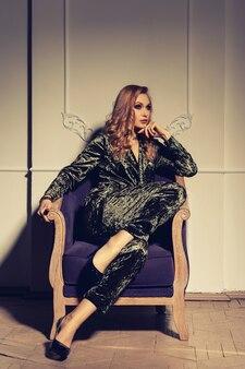 멀리보고 화려한 골동품 나무 안락의 자에 세련된 이브닝 가운에 앉아 아름 다운 젊은 여자의 초상화