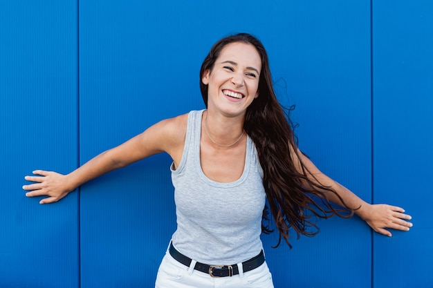 笑顔と青い壁を背景にポーズをとって美しい若い女性の肖像画