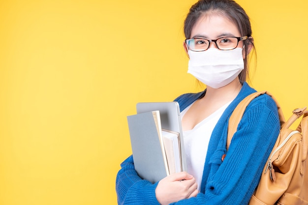 아름 다운 젊은 여자 학생의 초상화는 교과서를 들고 마스크를 착용-온라인 전자 학습 시스템을 공부