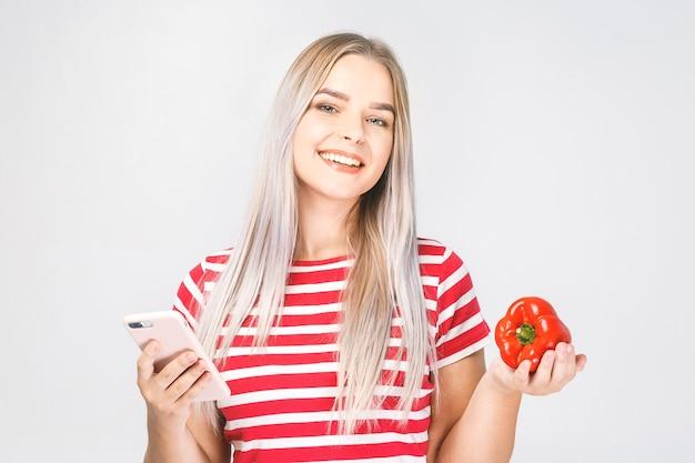 Портрет красивой молодой женщины с помощью мобильного телефона с овощами