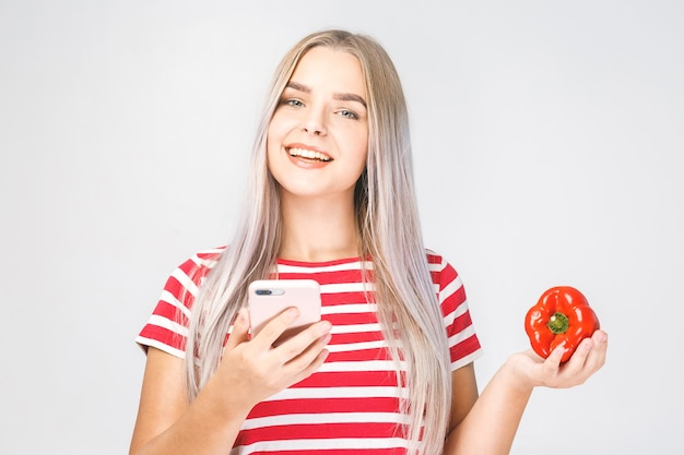 野菜と携帯電話を使用して美しい若い女性の肖像画