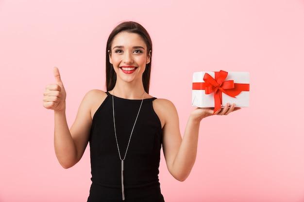 Портрет красивой молодой женщины в черном платье, стоящей изолированно на розовом фоне, держа подарочную коробку, показывая пальцы вверх