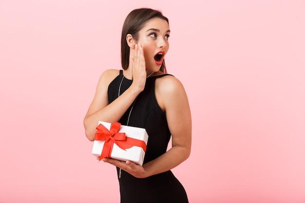 Портрет красивой молодой женщины в черном платье, стоящей изолированно на розовом фоне, держа подарочную коробку и глядя в сторону