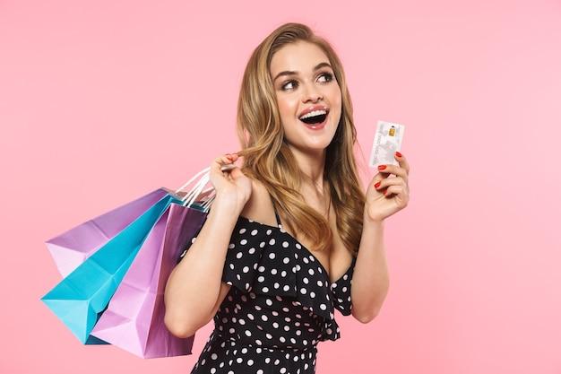 ピンクの壁に孤立して立っているドレスを着て、買い物袋を運んで、クレジットカードを示す美しい若い女性の肖像画
