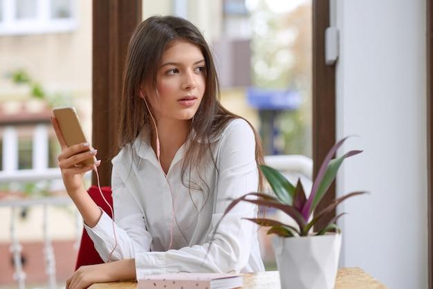 カフェのビデオ通話会議で彼女のスマートフォンを使用してイヤホンを着ている美しい若い女性の肖像画の人々ライフスタイル通信接続キャリア3 g 4 gモビリティの概念。
