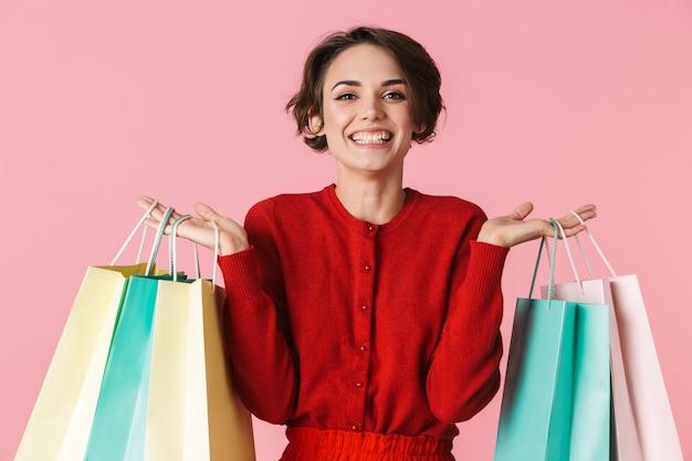 Портрет красивой молодой женщины в красной одежде, стоящей изолированно, с сумками для покупок