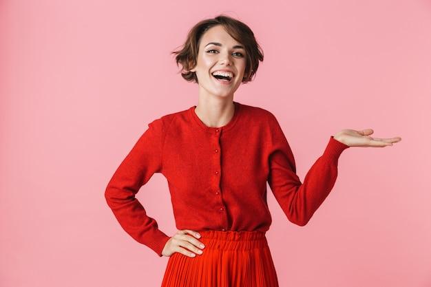 Портрет красивой молодой женщины в красной одежде, стоящей изолированно на розовом фоне, представляя пространство для копирования