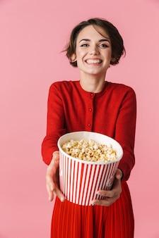 Портрет красивой молодой женщины в красном платье стоит изолированно на розовом фоне и ест попкорн