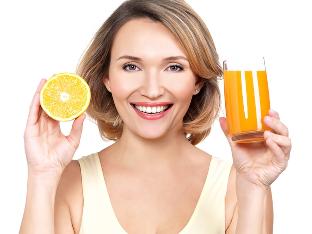 白で隔離のジュースとオレンジのガラスを持つ美しい若い女性の肖像画。