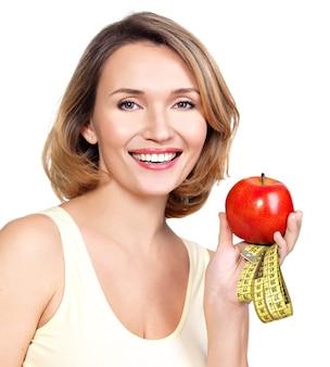 白で隔離の巻尺とリンゴを持つ美しい若い女性の肖像画。