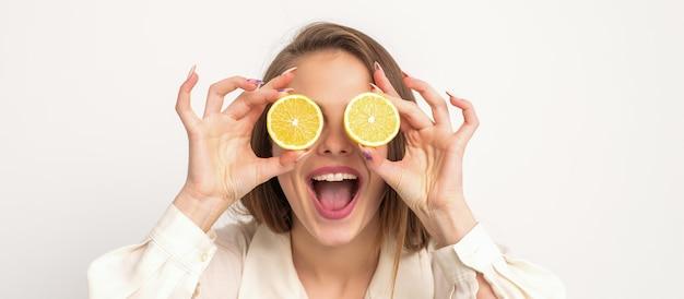 Портрет красивой молодой женщины с открытым ртом, держащей в глазах две дольки апельсина на фоне белой стены
