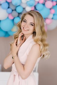 繊細なドレスで巻き毛のブロンドの髪を持つ美しい若い女性の肖像画