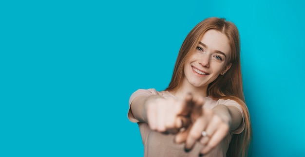 青いスタジオの背景に分離されたあなたを指差しながら笑顔のカメラを見てそばかすと赤い髪の美しい若い女性の肖像画。