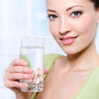 Портрет красивой молодой женщины со стаканом воды