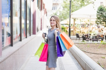Portrait of a beautiful young woman with multi colored shopping bags