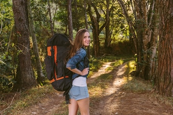 Portrait of a beautiful young woman with rucksack standing in forest