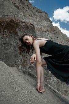 枯れ木の枝に美容ファッションの女性の肖像画。砂の山を背景に女の子