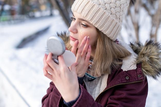 Портрет красоты молодая женщина, применяя увлажняющий крем для лица