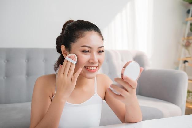 Sponge with powder를 사용하여 거울을 보고 있는 뷰티 젊은 여성 화장품의 초상화.