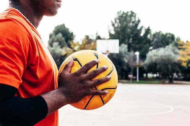 도시 농구 코트에서 그의 가슴에 농구를 들고 흑인 아프리카 계 미국인 소년의 초상화. 플레이 할 준비가되었습니다.