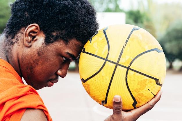 도시 농구 코트에 그의 마에 농구를 들고 흑인 아프리카 계 미국인 소년의 초상화.