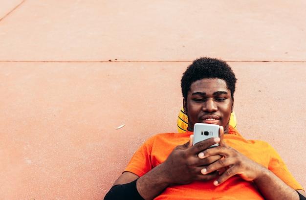 그의 농구에 누워 및 도시 농구 코트에서 자신의 휴대 전화로 탐색 흑인 아프리카 계 미국인 소년의 초상화. 오렌지색 티셔츠를 입고.