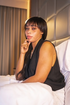 コンピューターで作業しているホテルのベッドで黒人のアフリカの民族の女の子の肖像画。仕事、ライフスタイルの新しい正常性。縦の写真