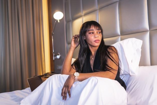 コンピューターで作業しているホテルのベッドで黒人のアフリカの民族の女の子の肖像画。作品、ライフスタイルの新しい正常性