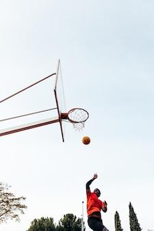 공을 쏠 바구니에 점프 흑인 아프리카 소년의 초상화. 도시 코트에서 농구