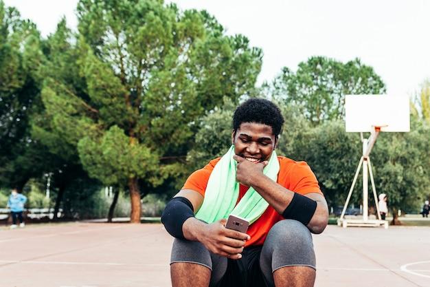 彼のボールに座って、バスケットボールコートで彼の電話を使用している黒人のアフロ少年の肖像画。コンセプトテクノロジーとスポーツ。